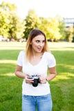 Leuk meisje die op zonnige dag in parkeren met haar camera lopen royalty-vrije stock afbeeldingen