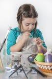 Leuk meisje die paaseieren schilderen Stock Foto's
