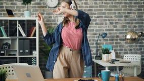 Leuk meisje die pret in bureau dansen hebben die aan muziek in hoofdtelefoons het rusten luisteren stock videobeelden