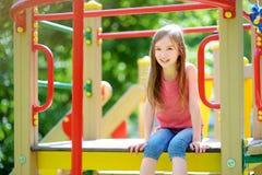 Leuk meisje die pret op een speelplaats hebben in openlucht stock fotografie