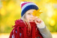 Leuk meisje die pret op mooie de herfstdag hebben Het gelukkige kind spelen in de herfstpark Jong geitje die geel dalingsgeblader Royalty-vrije Stock Afbeelding