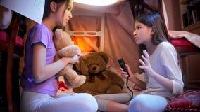 Leuk meisje die in pyjama's eng verhaal vertellen aan haar vriend in selfmadetent bij slaapkamer royalty-vrije stock fotografie