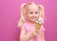Leuk meisje die roomijs op kleurenachtergrond eten Royalty-vrije Stock Afbeeldingen