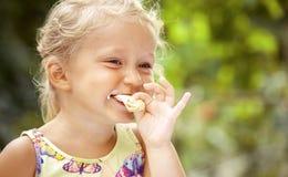 Leuk meisje die Roomijs op kleurrijke achtergrond eten stock foto
