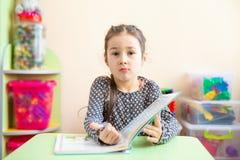 Leuk meisje die thuiswerk, het lezen van een boek, het kleuren van pagina's, het schrijven en het schilderen doen De kinderen sch royalty-vrije stock fotografie