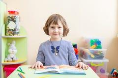 Leuk meisje die thuiswerk, het lezen van een boek, het kleuren van pagina's, het schrijven en het schilderen doen De kinderen sch stock afbeelding