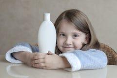 Leuk meisje die verschillende witte schoonheidstoiletries in haar handen houden, die de camera bekijken Babybad, hygiënetoebehore royalty-vrije stock foto's