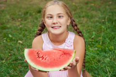 Leuk meisje die watermeloen op het gras in de zomertijd eten met paardestaart lang haar en toothy glimlachzitting op gras en enjo stock foto