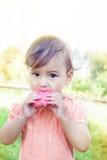 Leuk meisje die watermeloen op het gras in zomer eten Royalty-vrije Stock Foto