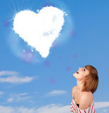 Leuk meisje die witte hartwolk bekijken op blauwe hemel Royalty-vrije Stock Foto