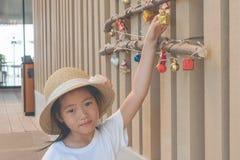 Leuk meisje die witte t-shirt en weefselhoed dragen, verfraait zij de giftdoos van holdingskerstmis op houten muur in haar hand royalty-vrije stock foto