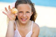 Leuk meisje die zeeschelp op strand tonen. Royalty-vrije Stock Foto