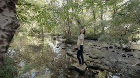 Leuk meisje die zich op een rots in het midden van de rivier bevinden stock footage