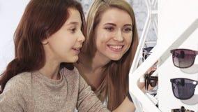 Leuk meisje die zonnebril met haar oudere zuster kiezen bij de opslag stock footage