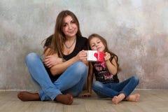 Leuk meisje en haar mooie jonge moederzitting samen op de vloer stock fotografie