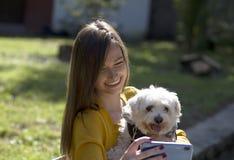 Leuk meisje en het witte hond stellen Foto's met mobiele telefoon stock foto