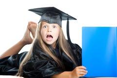 Leuk meisje in graduatiekleding met blauw boe-geroep Stock Foto's