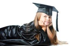 Leuk meisje in graduatiekleding op geïsoleerdd w Stock Afbeelding