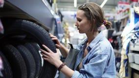 Leuk meisje in groot winkelcentrum die autobanden selecteren onderzoek koper Rijen van verschillende autobanden Zachte nadruk stock footage