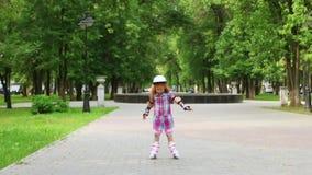 Leuk meisje in helmrolschaatsen in groen de zomerpark stock footage