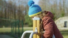 Leuk meisje in het blauwe hoed spelen op de speelplaats Wijfje die de carrousel en het glimlachen aanzetten Onbezorgde kinderjare stock video