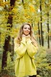 Leuk meisje in het goede stemming stellen in de herfstdag Openluchtmanierfoto van jonge mooie dame omringde de herfstbladeren royalty-vrije stock fotografie