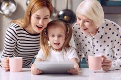 Leuk meisje het letten op beeldverhaal op tablet met moeder en grootmoeder stock afbeelding