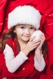 Leuk meisje in Kerstmishoed op rode achtergrond Royalty-vrije Stock Afbeeldingen