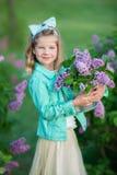 Leuk meisje in matrozen met fee luchtige rok die zich dicht bij lilac struik bevinden stock afbeeldingen