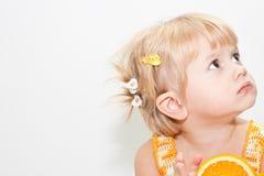 Leuk meisje met blonde haar en sinaasappel stock fotografie