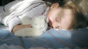 Leuk meisje met blonde haarslaap op het bed en aangestoken door de zon met een teddy konijntje stock video