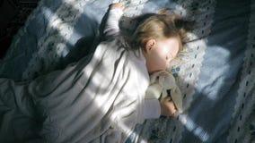 Leuk meisje met blonde haarslaap op het bed en aangestoken door de zon met een teddy konijntje stock footage
