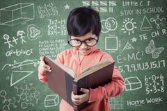 Leuk meisje met boek en krabbels op bord Stock Fotografie