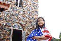 Leuk meisje met de vlag van de V.S. in huis Stock Foto's
