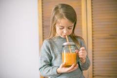 Leuk meisje met glas jus d'orange thuis royalty-vrije stock fotografie