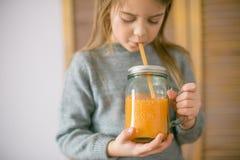 Leuk meisje met glas jus d'orange thuis stock afbeeldingen