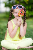 Leuk meisje met grote kleurrijke lolly Stock Foto