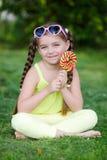 Leuk meisje met grote kleurrijke lolly Stock Foto's