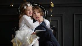 Leuk Meisje met haar broerpret die een digitale tabletcomputer, kinderen op laptop spelen en omhelzingen, Vrolijke Kerstmis gebru stock video