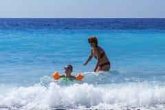 Leuk meisje met haar moeder die leren te zwemmen Stock Afbeeldingen