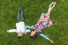Leuk meisje met haar weinig broer die op het groene gras liggen Stock Fotografie