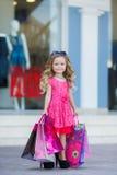 Leuk meisje met kleurrijke zakken voor het winkelen in supermarkt Royalty-vrije Stock Afbeeldingen