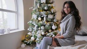 Leuk meisje met krullen die op camerazitting op bank dichtbij groene Kerstmisboom stellen met speelgoed op Kerstmisvooravond stock footage