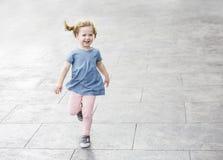 Leuk meisje met krullend en haar die in openlucht lopen lachen De ruimte van het exemplaar stock fotografie