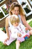 Leuk meisje met mamma in tuin Stock Afbeeldingen
