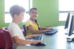 Leuk meisje met mannelijke klasgenoot die computer met behulp van stock fotografie