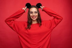 Leuk meisje in muisoren die op rode achtergrond stellen stock afbeelding