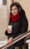 Leuk meisje in oordopjes met koffiekop Stock Afbeelding