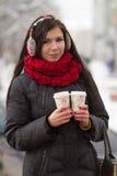 Leuk meisje in oordopjes met koffiekop Stock Fotografie