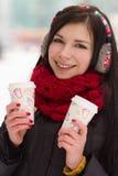 Leuk meisje in oordopjes met koffiekop Stock Foto